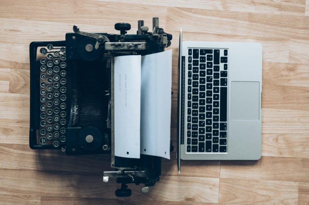 A typewriter next to a laptop.