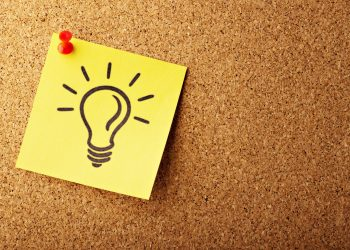 image of a light bulb on a sticky note pinned to a cork board