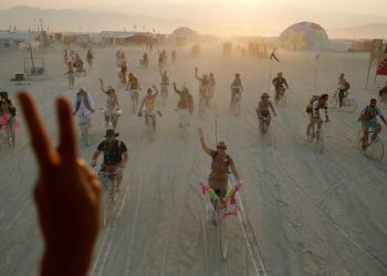Burning Man participants give peace sign and wave during the Burning Man arts and music festival in the Black Rock Desert of Nevada
