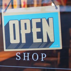 An open sign hanging in a store window.
